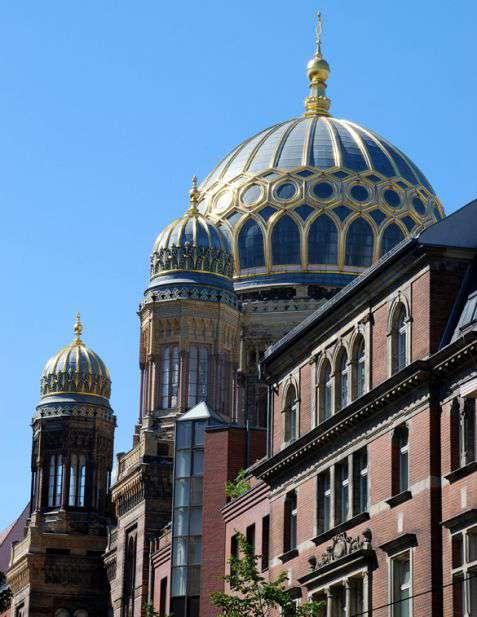 """Berlin. Nowa Synagoga (Neue Synagoge) z charakterystycznymi kopułami, przy Oranienburgerstrasse. Synagoga powstała w latach 1859–1866 według projektu Eduarda Knoblaucha i Friedricha Augusta Stülera jako symbol asymilacji niemieckich Żydów. Podczas pogromu w 1938 roku, """"nocy kryształowej"""" (Kristallnacht), została spalona przez bojówki hitlerowskie. W NRD stała jako zabezpieczona ruina. W latach dziewięćdziesiątych XX wieku została zrekonstruowana i ponownie uroczyście otwarta. Fot. Piotr Piluk (2004)"""